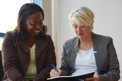 Mujeres maduras blancos y negros que trabajan junto Imagen de archivo libre de regalías