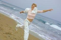 Mujeres maduras hermosas que se ejecutan en una playa Imagen de archivo libre de regalías