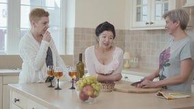 Mujeres maduras que comunican charlando en casa la colocación cerca de la tabla moderna en el medio de cocina Una señora que cort metrajes