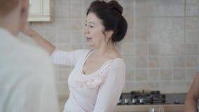 Mujeres maduras que comunican la charla en la cocina en casa Señora que cuenta historia interesante emocionalmente, activamente almacen de video