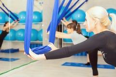 Mujeres maduras que hacen ejercicio aéreo de la yoga o yoga antigravedad Foto de archivo