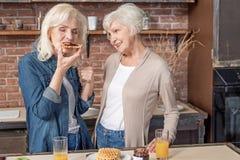 Mujeres maduras que prueban las galletas con el atasco en cocina Imágenes de archivo libres de regalías