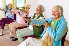 Mujeres mayores alegres que ejercitan sus brazos Foto de archivo