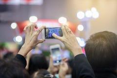 Mujeres mayores asiáticas que sostienen smartphone y que golpean ligeramente la pantalla para tomar fotos de archivo