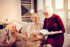 Mujeres mayores felices agradables que disfrutan de la literatura moderna foto de archivo libre de regalías
