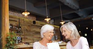 Mujeres mayores que discuten sobre la tableta digital 4k almacen de metraje de vídeo