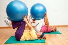 Mujeres mayores que ejercitan con las bolas del gimnasio Imagen de archivo libre de regalías