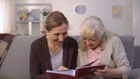 Mujeres mayores que miran a través de las fotos viejas en álbum de la familia, memorias del placer metrajes