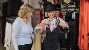 Mujeres mayores que seleccionan la ropa en tienda de la moda metrajes