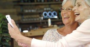 Mujeres mayores que toman un selfie en el café 4k metrajes