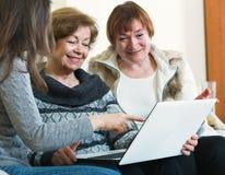 Mujeres mayores sonrientes de enseñanza de la muchacha linda que usan el ordenador portátil Imagen de archivo