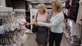 Mujeres mayores sonrientes que hacen compras en la tienda de ropa metrajes