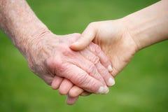 Mujeres mayores y jovenes que llevan a cabo las manos Imagen de archivo libre de regalías