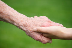 Mujeres mayores y jovenes que llevan a cabo las manos Foto de archivo libre de regalías