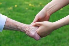 Mujeres mayores y jovenes que llevan a cabo las manos Imagen de archivo