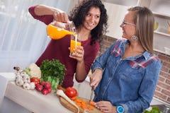 Mujeres modernas, el cocinar y diversión en la cocina Fotos de archivo libres de regalías
