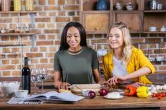 Mujeres multiétnicas jovenes que ruedan la pasta de la pizza mientras que cocina junto en cocina Fotografía de archivo libre de regalías