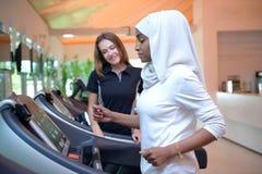 Mujeres musulmanes árabes jovenes de Emirati que se resuelven en un gimnasio imagen de archivo