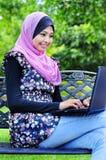 Mujeres musulmanes de un joven con una computadora portátil Imagen de archivo libre de regalías