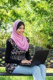 Mujeres musulmanes de un joven que usan una computadora portátil Fotografía de archivo libre de regalías