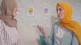 Mujeres musulmanes jovenes sordas hermosas del retrato dos en hijabs que hablan con lenguaje de signos en el cierre de la sala de almacen de metraje de vídeo