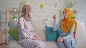 Mujeres musulmanes jovenes sordas hermosas del retrato dos en hijabs que hablan con lenguaje de signos en la sala de estar almacen de video