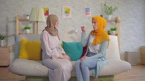 Mujeres musulmanes jovenes sordas hermosas del retrato dos en hijabs que hablan con lenguaje de signos en la sala de estar metrajes