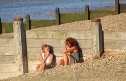 Mujeres nattering en la playa Imágenes de archivo libres de regalías