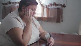 Mujeres obesas maduras que miden la presión con el sphygmomanometer digital mientras que se sienta en la tabla La mujer mayor est metrajes