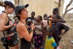 Mujeres occidentales que obran recíprocamente con los niños africanos en Malí Fotografía de archivo