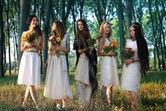 Mujeres paganas en el bosque que sostiene las flores imagen de archivo