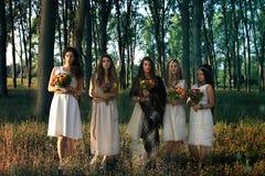 Mujeres paganas en el bosque que sostiene las flores foto de archivo