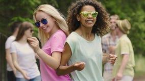 Mujeres positivas jovenes que bailan con los amigos al aire libre, celebración de la vida, diversión metrajes