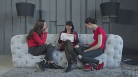 Mujeres positivas que miran la ropa del bebé en casa metrajes
