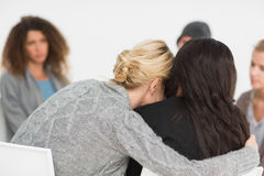 Mujeres que abrazan en grupo de la rehabilitación en la terapia Fotos de archivo libres de regalías