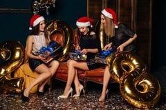 Mujeres que abren los regalos en la Navidad de la celebración Fotos de archivo libres de regalías