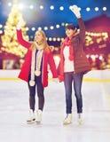 Mujeres que agitan las manos en la pista de patinaje de la Navidad Imagenes de archivo