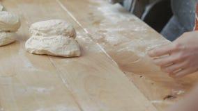 Mujeres que amasan la pasta del centeno para el pan en la tabla almacen de metraje de vídeo