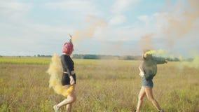 Mujeres que balancean con las bombas de humo coloreado al aire libre metrajes