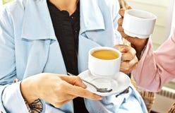 Mujeres que beben el café en la sonrisa del café Imágenes de archivo libres de regalías
