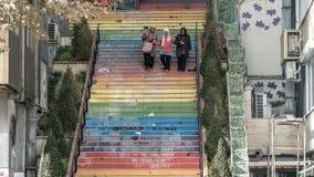 3 mujeres que caminan abajo de las escaleras pintadas en colores del arco iris en Estambul, Turquía Foto de archivo