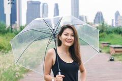 Mujeres que caminan el paraguas en el parque imagen de archivo libre de regalías