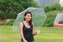 Mujeres que caminan en el paraguas en el césped fotos de archivo