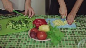 Mujeres que cocinan la comida en una cocina y que hablan cierre sano de la comida encima del tiro metrajes