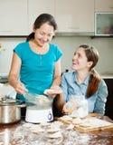 Mujeres que cocinan las bolas de masa hervida con el vapor eléctrico Imagenes de archivo