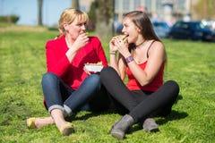 Mujeres que comen la hamburguesa y las patatas fritas Foto de archivo
