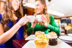 Mujeres que comen los molletes mientras que consumición del café Fotos de archivo