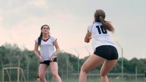 Mujeres que compiten en un torneo profesional del voleibol de playa Un defensor intenta parar un tiro durante las 2 mujeres almacen de video