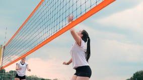 Mujeres que compiten en un torneo profesional del voleibol de playa Un defensor intenta parar un tiro durante las 2 mujeres metrajes