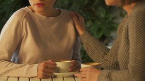 Mujeres que comunican sobre la taza de café, diciendo los secretos, apoyando en pena almacen de video